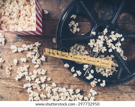 Cinema concept of vintage film reel with popcorn and movie tickets - stock photo