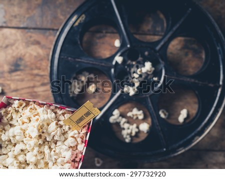 Cinema concept with vintage film reel, popcorn and a movie ticket - stock photo