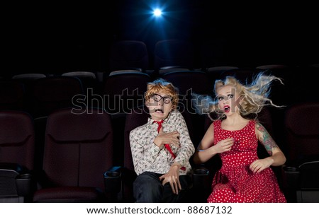 Cinema date, shocked couple is watching a scary movie - stock photo