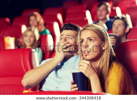 cinema, entertainment and people concept - couple drinking soda and watching horror, drama or thriller movie in theater - stock photo