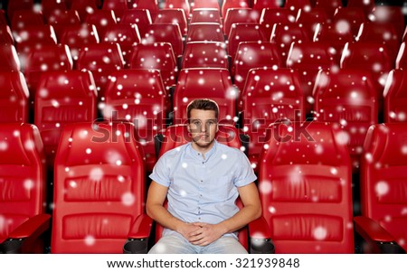 cinema, entertainment and people concept - happy young man watching movie alone in empty theater auditorium with snowflakes - stock photo