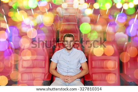 cinema, entertainment and people concept - happy young man watching movie alone in empty theater auditorium - stock photo