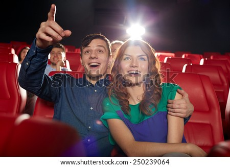 cinema, entertainment, gesture, emotions and people concept - happy friends watching movie pointing finger to screen in theater - stock photo
