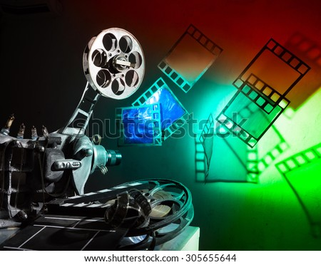 Cinema projector and a film pieces on the bright background - stock photo