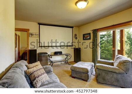 Cinema room in American house with projector screen on the wall, furnished with comfortable gray sofas - stock photo