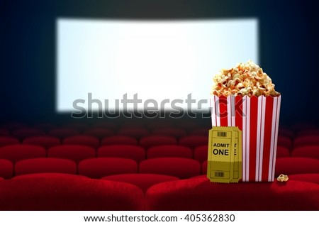 Cinema seat and pop corn facing empty movie screen - stock photo