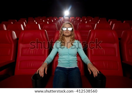 cinema, technology, entertainment and people concept - young woman with 3d glasses watching movie alone in empty theater auditorium - stock photo