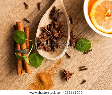 Cinnamon and anise on wooden background with tea - stock photo