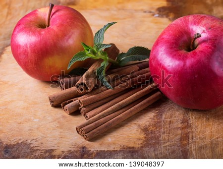 Cinnamon and apples on wooden background. Selective focus.