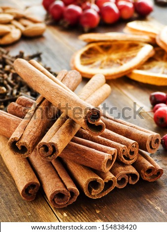 Cinnamon and other christmas spices, fruits, nuts and berries. Shallow dof. - stock photo
