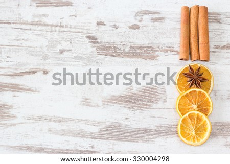Cinnamon, anise and orange slices on wooden background