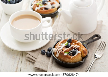Cinnamon bun for one in a tiny cast iron skillet - stock photo