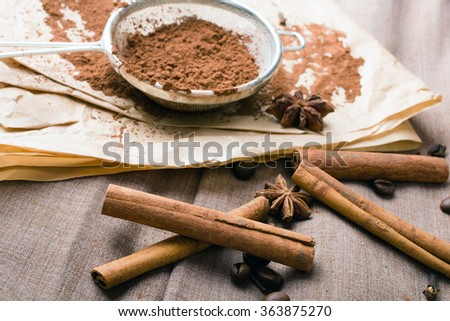 cinnamon, coffee beans, cocoa and anise on baking paper - stock photo