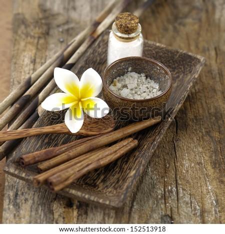 cinnamon, frangipani salt in bowl on driftwood ,  - stock photo