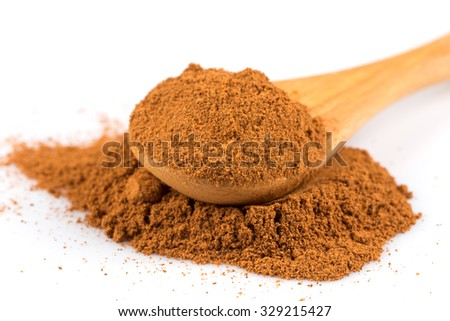 cinnamon ground and spoon isolated on a white background
