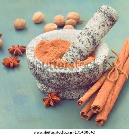 cinnamon powdered in mortar  with anise and nutmeg on wooden table - stock photo