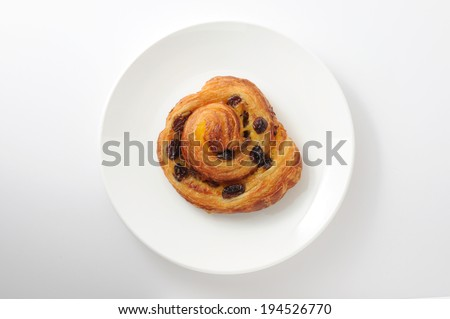 Cinnamon raisin roll cake on plate isolated on white background  - stock photo