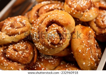 Cinnamon rolls in a metal container against a dark background - stock photo