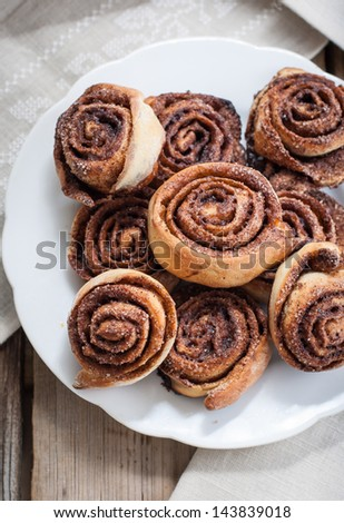 Cinnamon rolls on a plate on a wooden background - stock photo