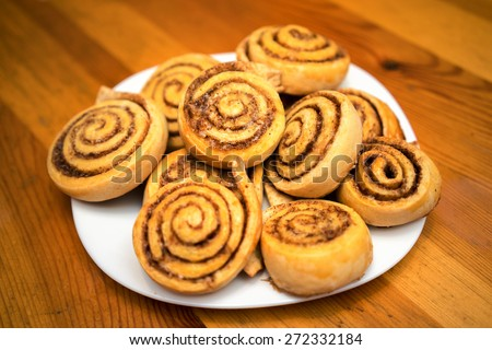 cinnamon rolls on a white dish in a wooden table - stock photo
