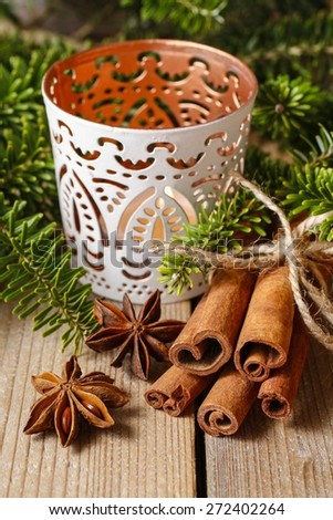 Cinnamon sticks and anise stars on christmas table. Beautiful candle holder in the background. - stock photo
