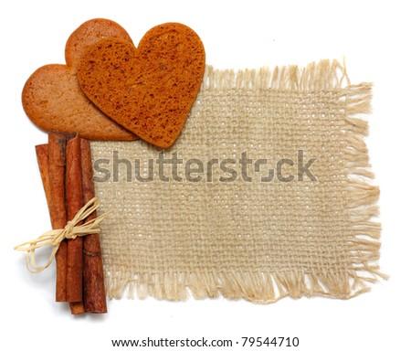 Cinnamon sticks and cookies on sack - stock photo