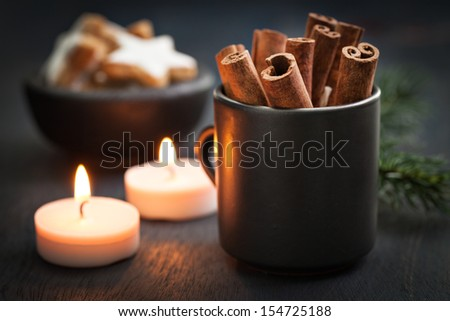 cinnamon sticks and cookies on wooden background - stock photo