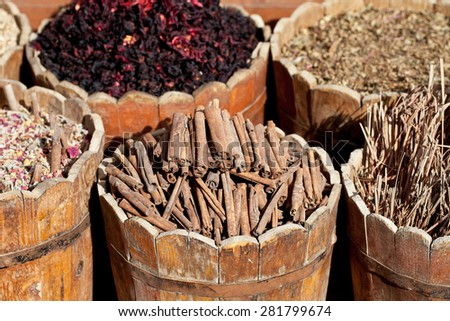 cinnamon sticks and  dried hibiscus petals in wooden container on street stall in tropical country