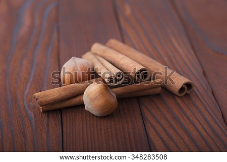 Cinnamon sticks and hazelnuts in shell on wooden background