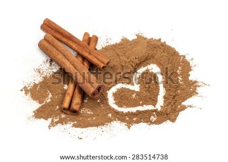 Cinnamon sticks and Heart shape hand drawn in cinnamon powder on white background - stock photo