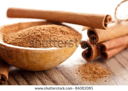 Cinnamon sticks and meal close up on wooden table - stock photo