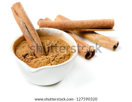 Cinnamon sticks and meal isolated on white. Selective focus - stock photo