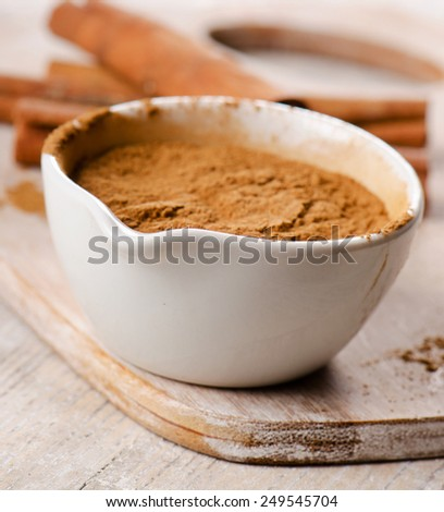 Cinnamon sticks and meal  on wooden board. Selective focus - stock photo
