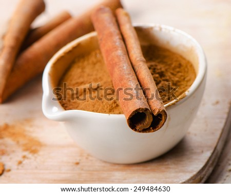 Cinnamon sticks and meal . Selective focus - stock photo
