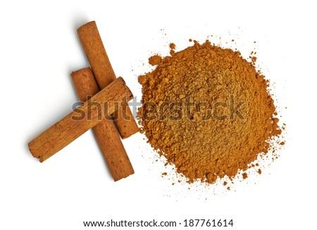 Cinnamon sticks and powder pile on white background - top view - stock photo