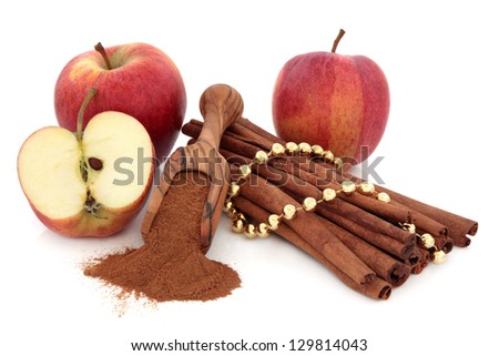 Cinnamon sticks and powder with gala apple fruit and gold bead chain over white background.