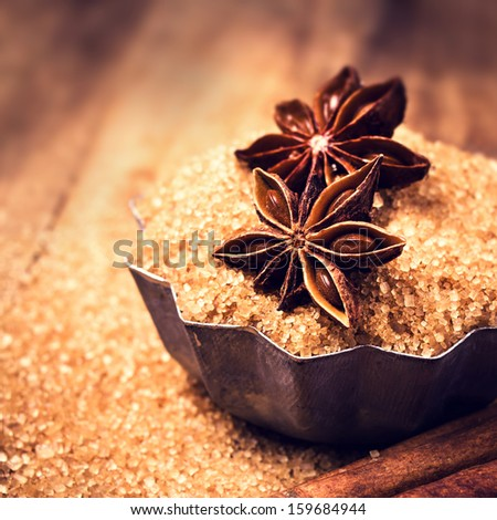 Cinnamon sticks and star anise on cane sugar on wooden background macro. Christmas card. - stock photo