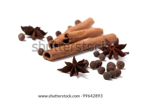 Cinnamon sticks, anise stars and black peppercorns on white background