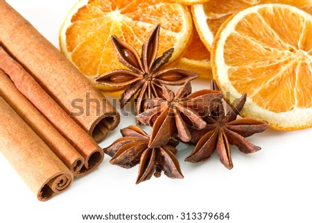 Cinnamon sticks, anise stars and orange slices on white background - stock photo