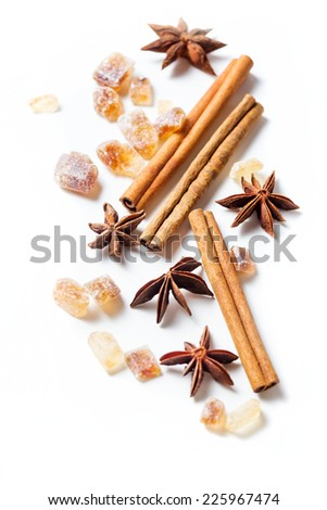 Cinnamon sticks, brown sugar, anise stars on white background - stock photo