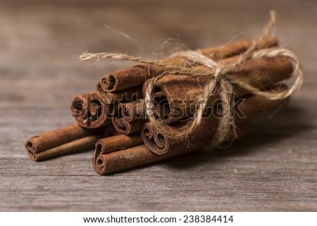 Cinnamon sticks close up on wooden background - stock photo