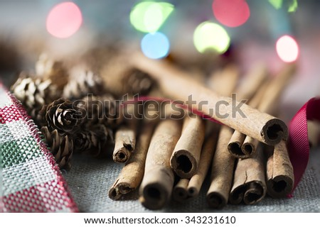 Cinnamon sticks close up with small pine cones and festive holiday lights in the background - stock photo