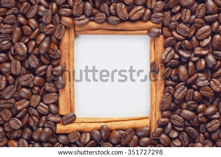 Cinnamon sticks decorative frame with blank white paper sheet inside surrounded by scattered coffee beans. Combination of coffee and cinnamon as ingredients of tasty aromatic drink. Place for text. - stock photo