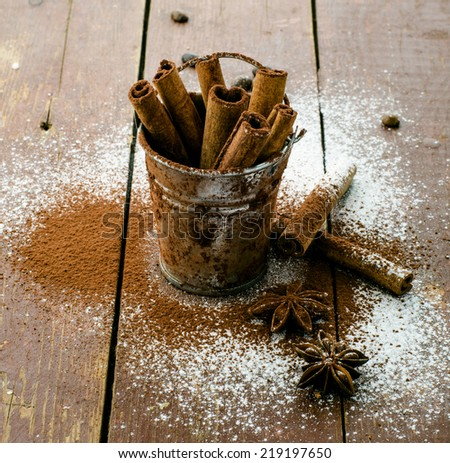 Cinnamon sticks in bucket on wooden background and stars of anise - stock photo