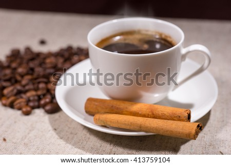 Cinnamon sticks in focus beside hot coffee in teacup and saucer with beans scattered in background on tablecloth