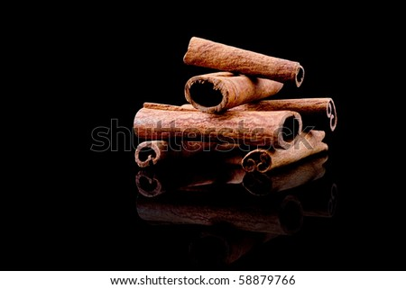 cinnamon sticks on black background with reflection