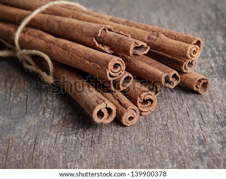 cinnamon sticks on old wooden table, selective focus - stock photo