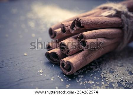 cinnamon sticks over black stones background at christmas time  - stock photo