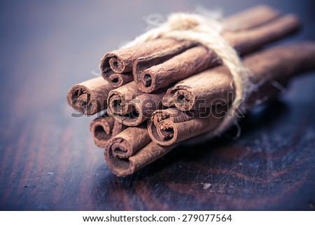 cinnamon sticks over black stones background at christmas time  - stock photo