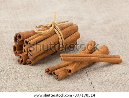 Cinnamon sticks staked on tissue background closeup - stock photo